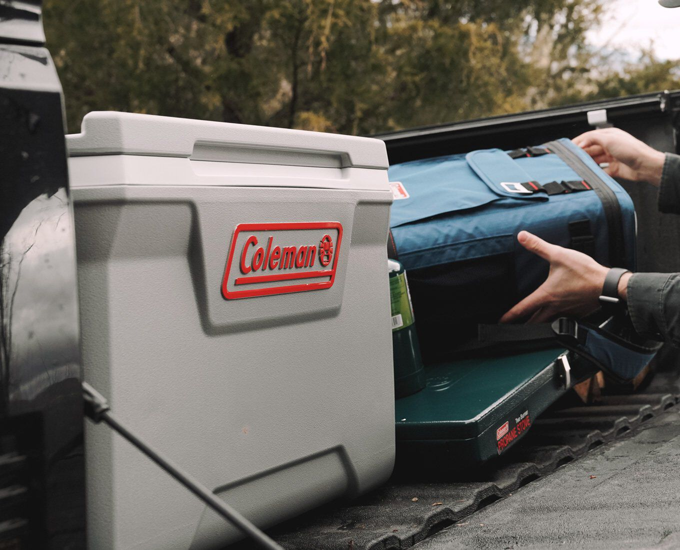 assorted outdoor camping gear being loaded into pickup truck