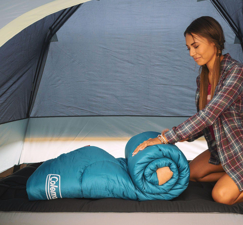 woman rolling sleeping bag on air mattress inside tent